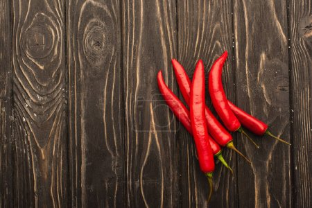 top view of chili peppers on wooden surface