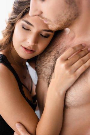 Photo pour Foyer sélectif de la femme avec les yeux fermés touchant homme torse nu - image libre de droit