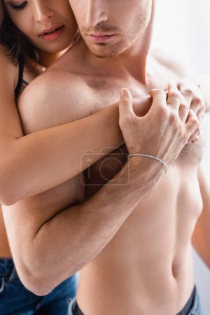 Photo for Cropped view of woman hugging muscular man isolated on white - Royalty Free Image