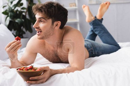 selective focus of shirtless and barefoot man lying on bed and holding bowl with ripe strawberries
