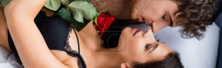 Photo for Panoramic concept of shirtless man and sensual woman with closed eyes lying with rose on bed - Royalty Free Image