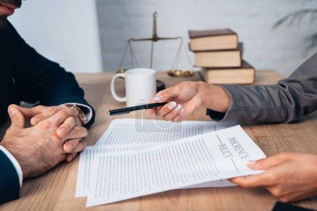 Photo pour Vue recadrée de l'avocat donnant stylo à l'homme d'affaires près contrat de police d'assurance en fonction - image libre de droit