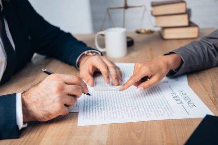 Photo pour Vue recadrée de l'avocat pointant du doigt le contrat de police d'assurance près de l'homme d'affaires avec stylo - image libre de droit