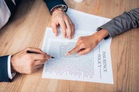 Photo pour Vue partielle de l'avocat pointant du doigt le contrat de police d'assurance près de l'homme d'affaires avec stylo - image libre de droit