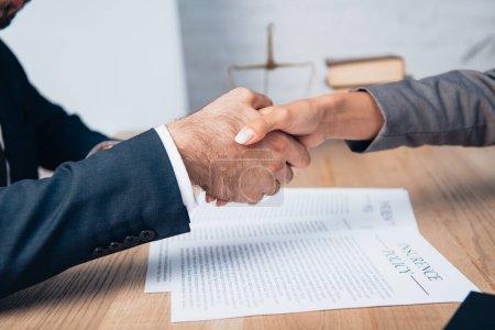 Photo pour Vue recadrée de l'homme d'affaires et de la femme d'affaires serrant la main près des documents - image libre de droit