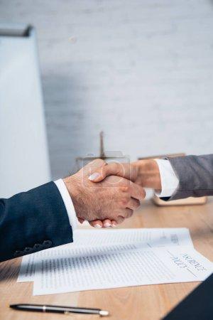 Photo pour Vue recadrée de l'homme d'affaires et de la femme d'affaires serrant la main près des documents de police d'assurance - image libre de droit