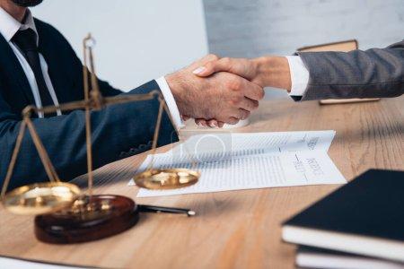 Photo pour Foyer sélectif de l'homme d'affaires et de la femme d'affaires serrant la main près des échelles dans le bureau - image libre de droit