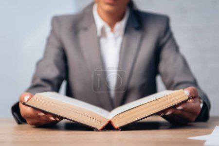 selective focus of lawyer in suit reading book in office