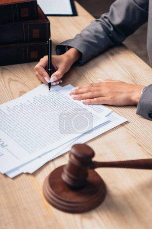 Photo pour Orientation sélective du juge signant le document de police d'assurance en fonction - image libre de droit