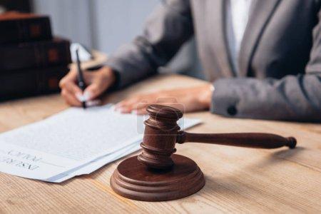 Photo pour Vue recadrée du juge signant le document de police d'assurance près du marteau - image libre de droit