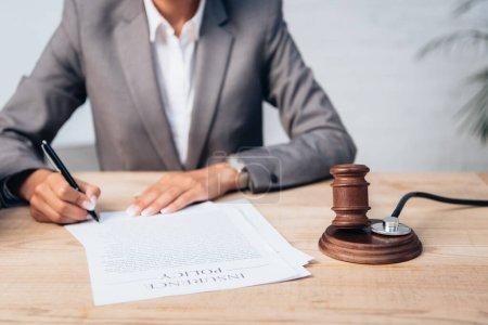 Photo pour Vue recadrée du juge signant contrat d'assurance près de gavel et stéthoscope - image libre de droit
