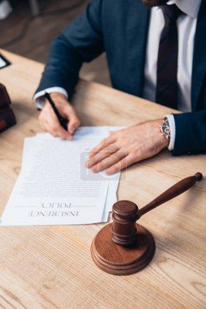 Photo pour Concentration sélective des documents de signature de juge avec le lettrage de police d'assurance près du marteau sur la table - image libre de droit