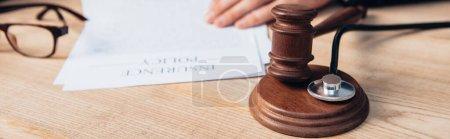 Photo pour Récolte panoramique de juge près de papiers avec lettrage de police d'assurance et marteau sur la table - image libre de droit