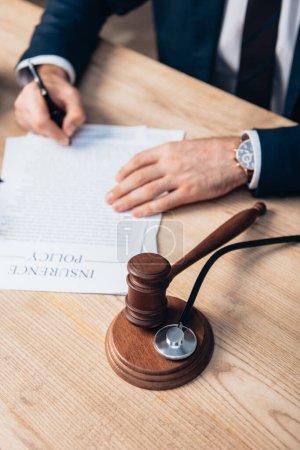 Photo pour Vue partielle des papiers de signature du juge avec lettrage de police d'assurance près du marteau et stéthoscope sur la table - image libre de droit