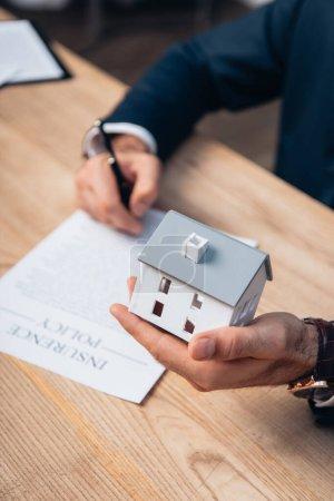 Photo pour Vue recadrée du modèle de maison de détention d'avocats près des documents avec lettrage de police d'assurance sur la table - image libre de droit