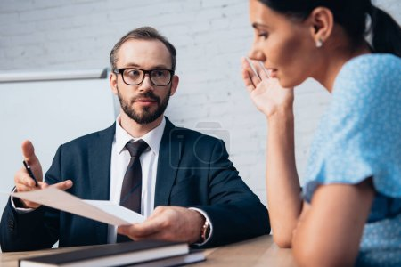 selective focus of bearded lawyer in glasses looking at client while holding document in office