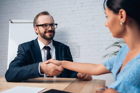 Photo pour Foyer sélectif de barbu avocat dans des lunettes serrant la main avec le client au bureau - image libre de droit