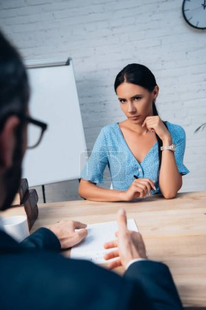 selective focus of woman looking at lawyer gesturing near insurance contract