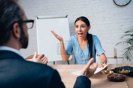 selective focus of brunette client screaming and gesturing while holding contract near lawyer in office