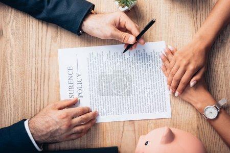 Photo pour Vue de dessus du stylo de tenue d'avocat près de l'accord de police d'assurance, tirelire, usine et femme - image libre de droit