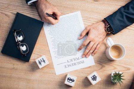 Photo pour Vue du dessus de l'avocat signant contrat de police d'assurance près de l'usine, lunettes, bloc-notes et cubes en bois avec la famille, voiture et maison - image libre de droit