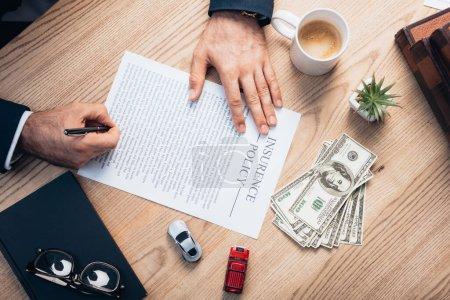 Photo pour Vue du dessus de l'avocat signant l'accord de police d'assurance près de l'usine, lunettes, cahier, dollars et jouets voitures - image libre de droit