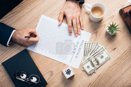 Photo pour Vue du dessus de l'avocat signant l'accord de police d'assurance près de l'usine, lunettes, cahier, dollars et cube avec la maison - image libre de droit
