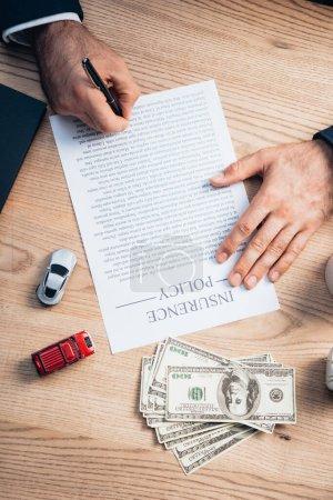 Photo pour Vue partielle de l'avocat signant l'accord de police d'assurance près de dollars et de jouets voitures - image libre de droit