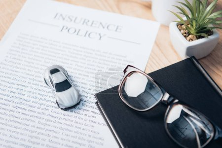 Photo pour Voiture jouet sur contrat de police d'assurance près de portable, plante et lunettes - image libre de droit