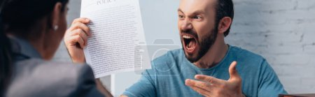 Photo for Panoramic shot of angry and bearded man screaming while holding insurance policy agreement near lawyer - Royalty Free Image
