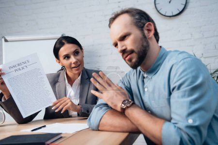 Photo for Selective focus of brunette lawyer holding insurance policy agreement near bearded man showing no gesture - Royalty Free Image