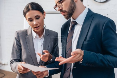Photo for Selective focus of businessman and businesswoman gesturing and looking at document in office - Royalty Free Image