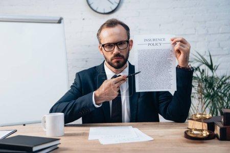 Photo pour Accent sélectif de l'avocat dans les lunettes tenant stylo et contrat avec le lettrage de la police d'assurance tout en regardant la caméra - image libre de droit