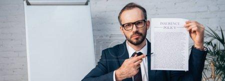 Photo pour Recadrage horizontal de l'avocat dans des lunettes et costume stylo et contrat avec lettre de police d'assurance au bureau - image libre de droit