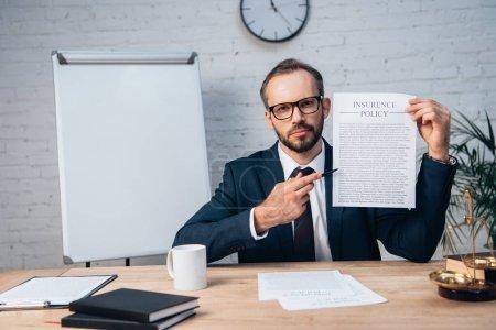 Photo pour Orientation sélective de l'avocat barbu dans les lunettes tenant stylo et contrat avec le lettrage de la police d'assurance en fonction - image libre de droit
