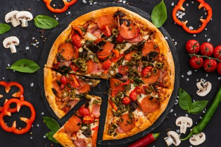 Photo pour Vue de dessus de délicieuses pizzas italiennes avec légumes et salami sur fond noir - image libre de droit