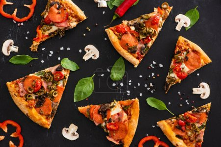 Photo for Top view of delicious Italian pizza slices with vegetables and salami on black background - Royalty Free Image