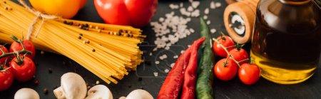 Photo pour Vue rapprochée des spaghettis italiens crus aux légumes sur fond noir, panoramique - image libre de droit