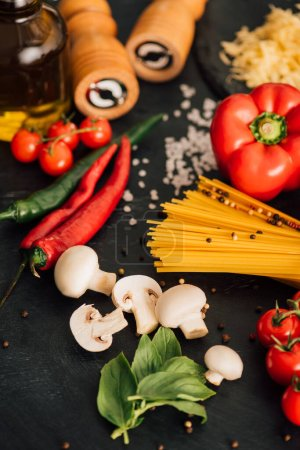selective focus of raw Italian spaghetti with vegetables on black background