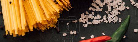 close up view of raw Italian spaghetti with salt on black background, panoramic shot