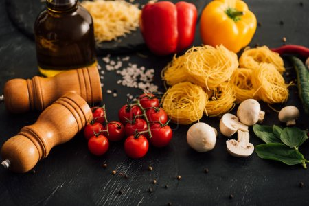 Photo for Raw Italian Capellini with vegetables on black background - Royalty Free Image