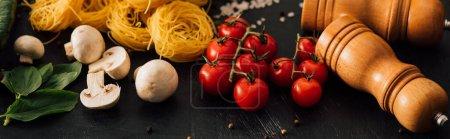 Photo pour Capellini italienne crue aux légumes et assaisonnement sur fond noir, panoramique - image libre de droit