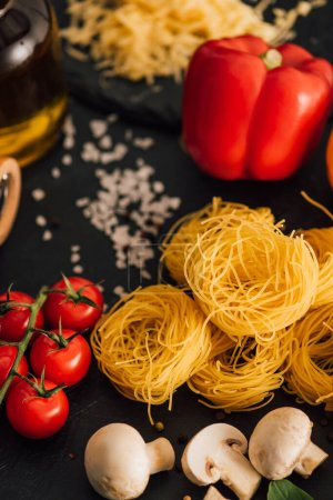 Photo for Selective focus of raw Italian Capellini with vegetables and salt on black background - Royalty Free Image