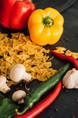 rohe italienische Farfalle mit Gemüse auf schwarzem Hintergrund