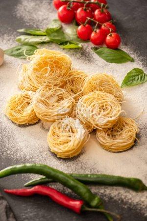 Photo pour Capellini italienne crue avec des légumes sur farine sur fond noir - image libre de droit