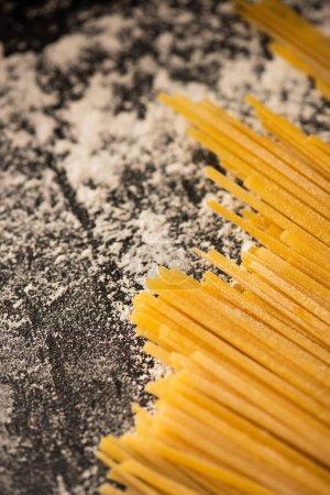 Photo pour Vue rapprochée des spaghettis crus et de la farine sur fond noir - image libre de droit