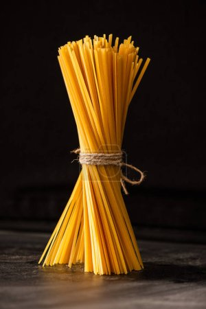 Photo for Tied uncooked Italian spaghetti isolated on black - Royalty Free Image