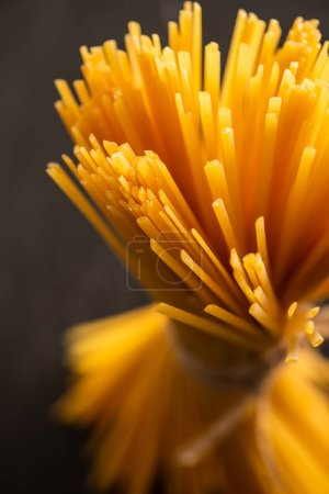 close up view of uncooked Italian spaghetti isolated on black