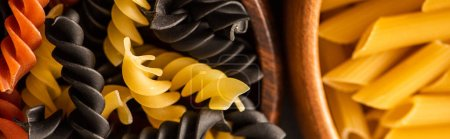 Photo pour Vue rapprochée des pâtes italiennes crues colorées dans des bols en bois - image libre de droit