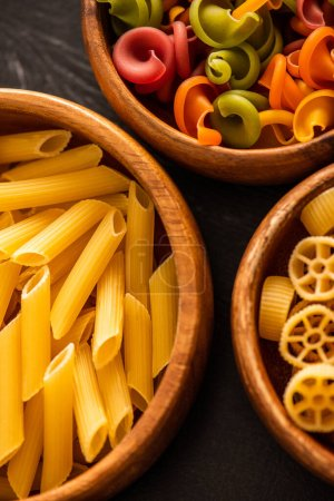 close up view of various raw Italian pasta in wooden bowls